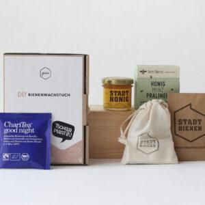 Kleine Geschenkbox mit ChariTea, Bienenwachstuch-DIY, Pralinen, Honig und Samenbombe