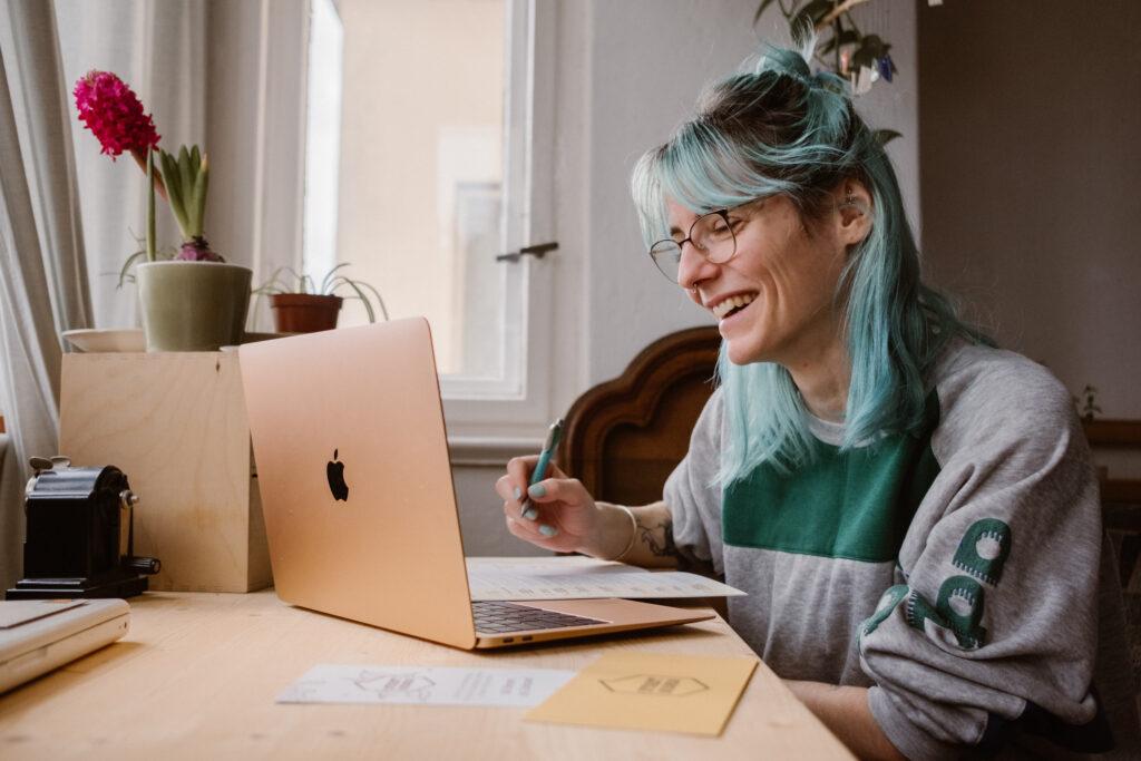Die Teilnehmerin des digitalen Orientierungsseminars sitzt mit den Kursmaterialien am Schreibtisch, schaut auf ihren Computerbildschirm und lächelt.