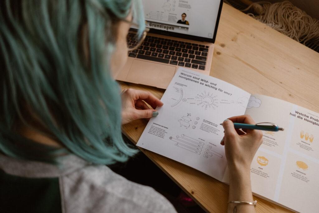 Die Teilnehmerin des digitalen Orientierungsseminars notiert etwas in ihren Seminarunterlagen.